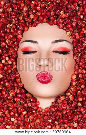 Beautiful woman lying in wild strawberry and air kiss