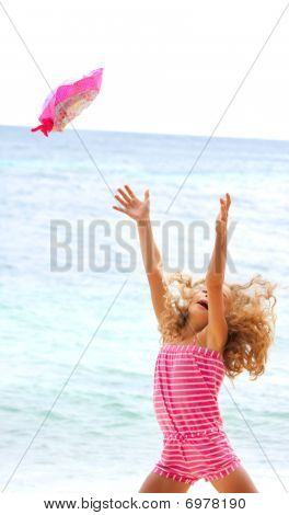 Happy Girl Throwing Her Hat Up On Sea Background