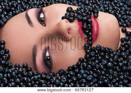 woman is eating blueberries lying in blueberries