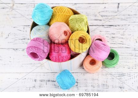 Clews of thread for hook knitting in box on wooden background