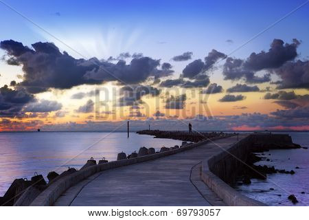 Sunset landscape with dark clouds,sunbeams and pier