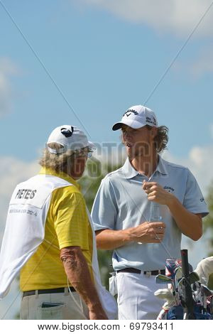 TSELEEVO, MOSCOW REGION, RUSSIA - JULY 26, 2014: Thomas Pieters of Belgium with his caddy during the M2M Russian Open. This international golf tournament is the stage of the European Tour