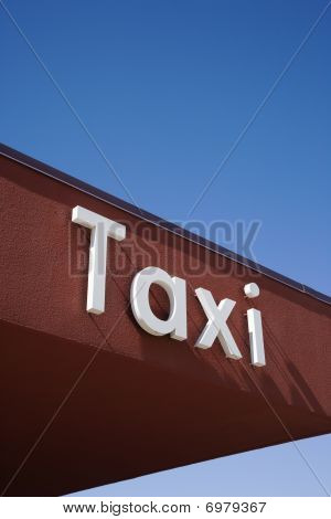 Taxi Sign On A Brown Wall