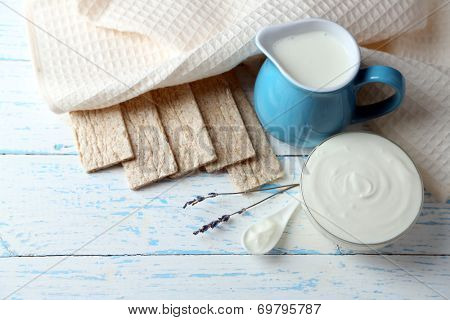 Homemade yogurt and tasty Tasty crispbread on wooden table background