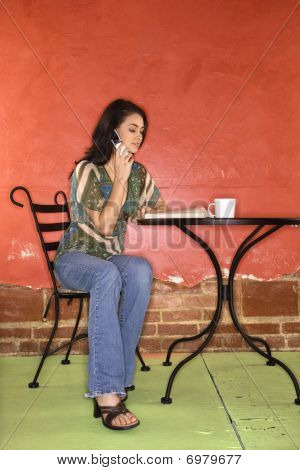 Young Woman Sitting And Talking On Cellphone
