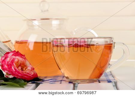 Kettle and cup of tea from tea rose on napkin on wooden background
