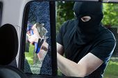 stock photo of mobsters  - Car thief with crowbar and broken glass - JPG