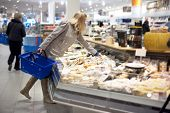 image of grocery-shopping  - young woman shopping for groceries and picking a piece of cheese from a display counter in a supermarket - JPG