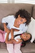 image of tickle  - Pretty mother sitting on the couch tickling daughter at home in the living room - JPG