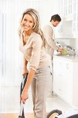 foto of house cleaning  - Housework vacuum cleaner young couple home kitchen - JPG