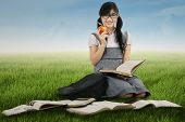 picture of indian apple  - Female student holding a red apple while studying outdoors - JPG