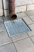 picture of downspouts  - Drain pipe with flowing rain water and drainage grate - JPG