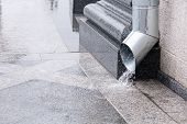 stock photo of downspouts  - Rain water run out of a downspout during a thunderstorm