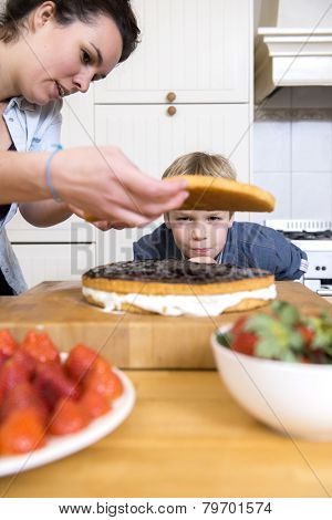 Young boy looking at a woman preparing layered cake in kitchen