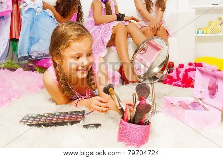 Girl laying on fluffy white carpet with brushes
