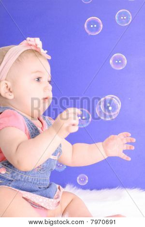 beautiful baby catching bubbles