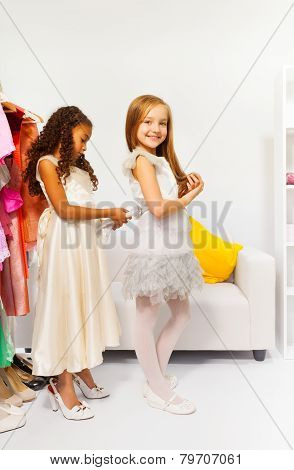 Small girl helps her friend by fitting the dress