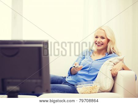 food, happiness and people concept - smiling young girl with popcorn watching movie at home