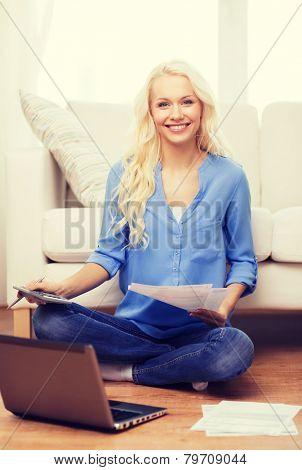 tax, finances, technology, home and happiness concept - smiling young woman with papers, laptop computer and calculator at home