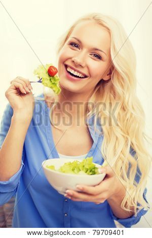 healt, dieting, home and happiness concept - smiling young woman with green salad at home