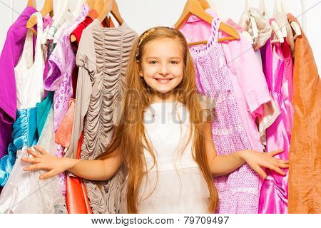 Smiling girl stands among dresses on hangers