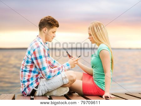 summer beach, vacation, technology, addiction and friendship concept - couple with smartphones sitting on bench over sunset at sea side