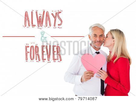 Handsome man holding paper heart getting a kiss from wife against always and forever