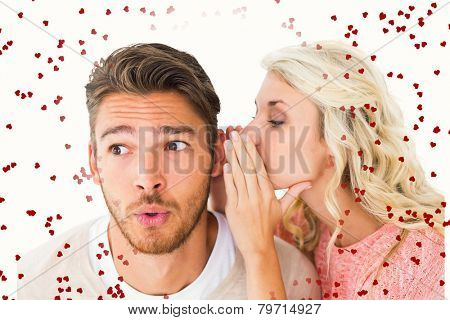 Attractive blonde whispering secret to boyfriend against red love hearts