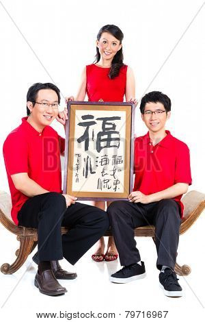 Family celebrates Chinese new year with traditional calligraphy, wearing red