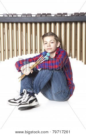 Teenage Boy Sits Under Marimba In Studio