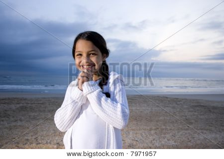 Cute Little Hispanic Girl Smiling On Beach At Dawn