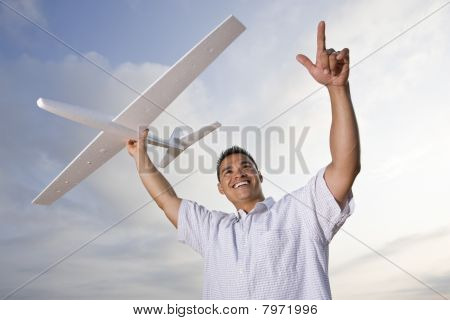 Hispanic Man Holding Model Airplane Glider Over Head