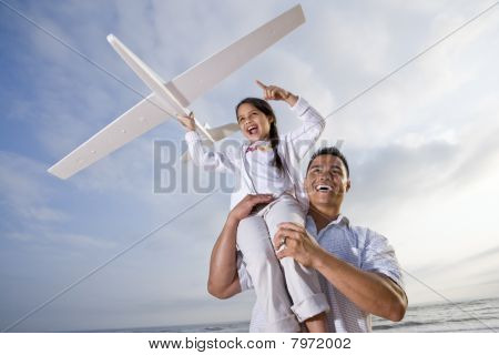Hispanic Dad Playing Holding Girl High On Shoulder