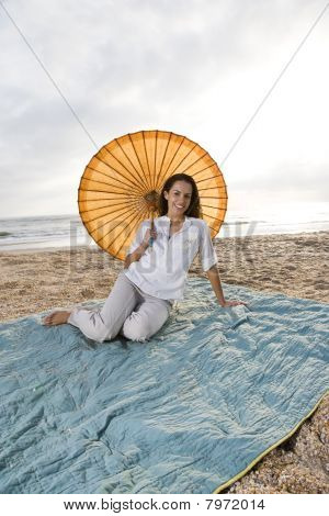 Hispanic Woman With Parasol On Beach Blanket