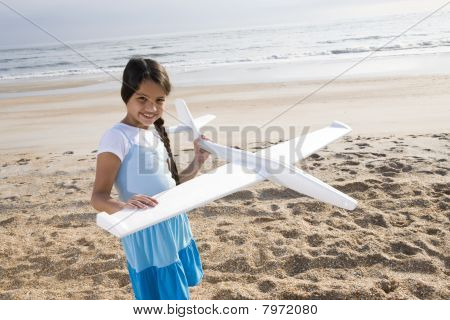 Hispanic Girl Playing With Toy Plane On Beach