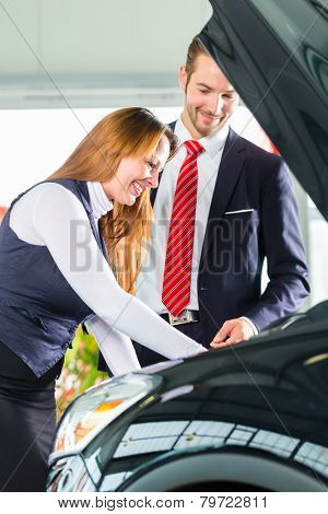 Seller or car salesman and female client or customer in car dealership presenting the engine performance of new and used cars in the showroom, the woman looks under the hood