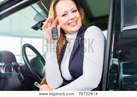 Young woman sits in new car on driver seat in a car dealership, obviously she is buying the auto, or she has bought the car and holding the keys in hand