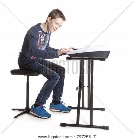 Teenage Boy Playing On Keyboard In Studio