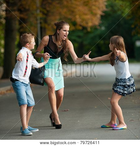 Mother with naughty son and daughter on a walk in park on summer evening