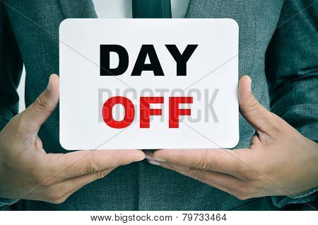 a young businessman showing a signboard with the text day off written in it