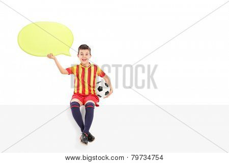 Junior football player holding a speech bubble seated on a panel isolated on white background