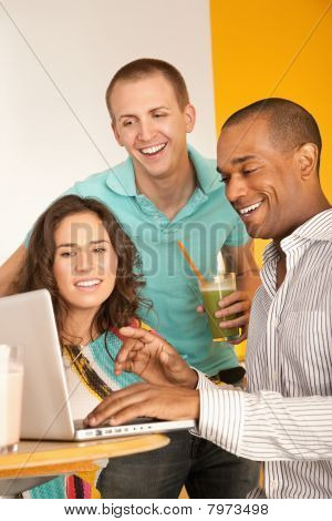 Three People Dining Out Using A Laptop