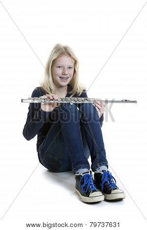 Young Blond Girl Sits And Holds Flute In Studio