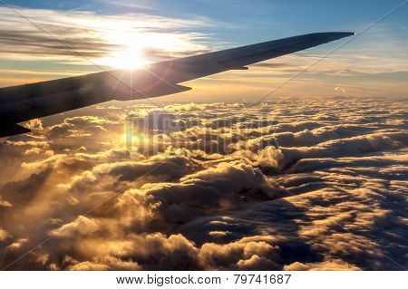 Silhouette Of Airplane Wing Against Golden Sunrise