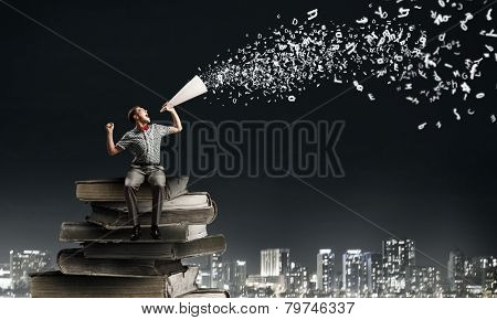 Young man sitting on pile of books and screaming in trumpet
