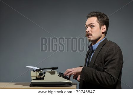 Happy young author typing at typewriter