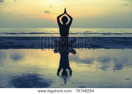 Silhouette of woman meditating on the beach. Yoga and fitness. In the Lotus posture with reflection in water.