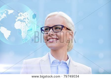 business, people, technology and education concept - young smiling businesswoman in eyeglasses with virtual screens and globe hologram outdoors