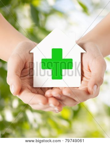 care, help, charity and people concept - close up of hands holding white paper house with green cross sign over natural background