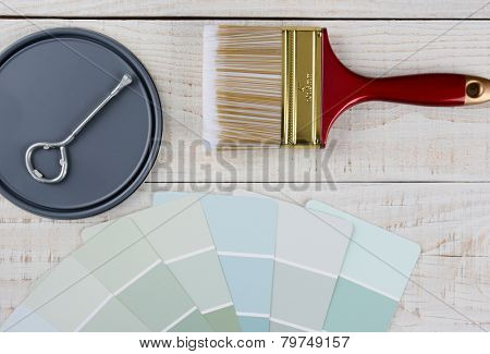 Overhead shot of  a paint can lid, opener, color samples and paint brush on a rustic wooden surface. Horizontal format with copy space.